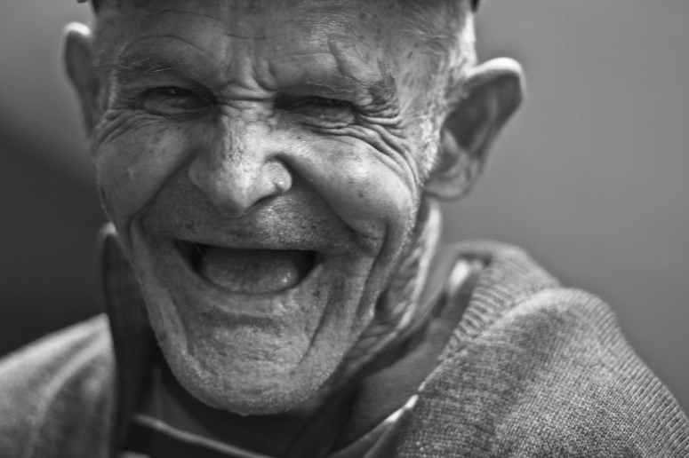 grayscale photo of laughing old man